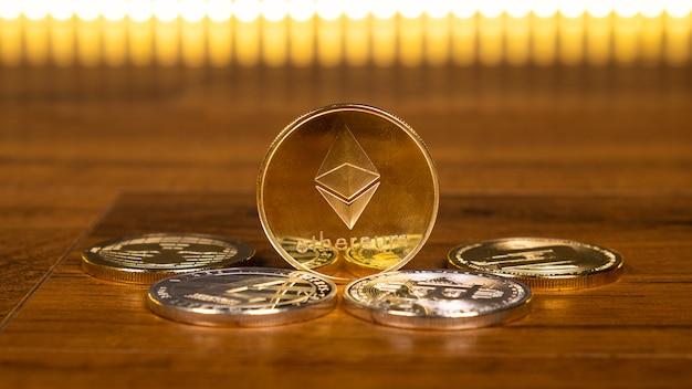 Złota moneta ethereum z różnymi monetami kryptowalutowymi z bliska, wirtualna waluta, wydobycie, koncepcja biznesowa.
