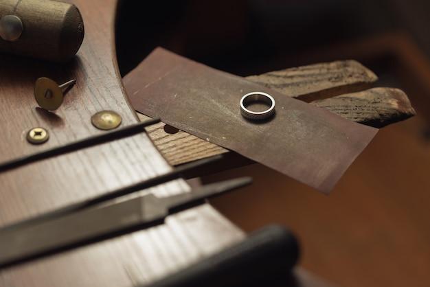 Złota obrączka z brylantami ręcznie polerowana przez jubilera, aby stworzyć klejnot wymaga precyzyjnego...