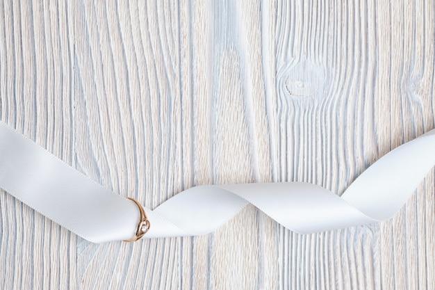 Złota obrączka ze wstążką na drewnianej przestrzeni. widok z góry.