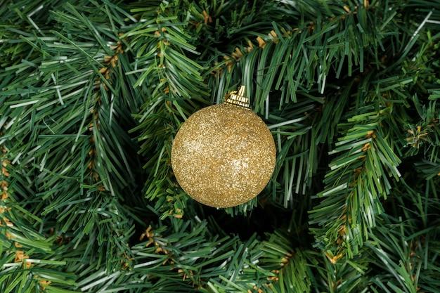 Złota piłka boże narodzenie na białym tle na gałęzi choinki.