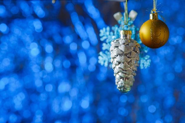 Złota piłka i srebrny stożek wiszące na świecącym tle bokeh.