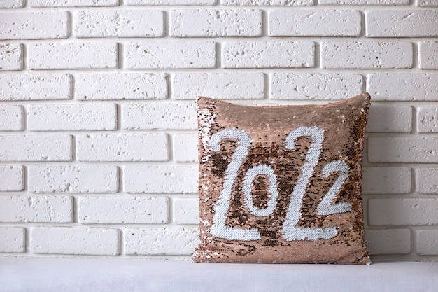 Złota poduszka z błyskotkami z napisem 2022 poduszka z cekinami na tle ceglanego muru