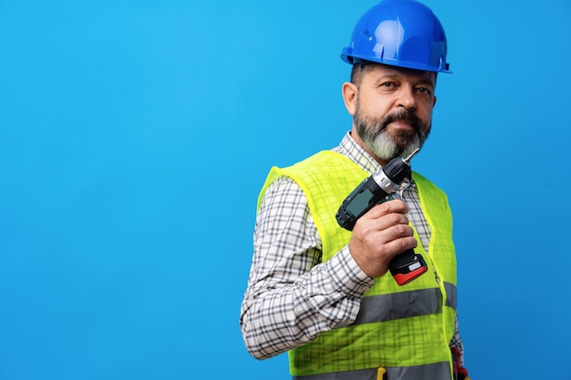 Złota rączka konstruktora w niebieskim kasku trzymającym śrubokręt na niebieskim tle