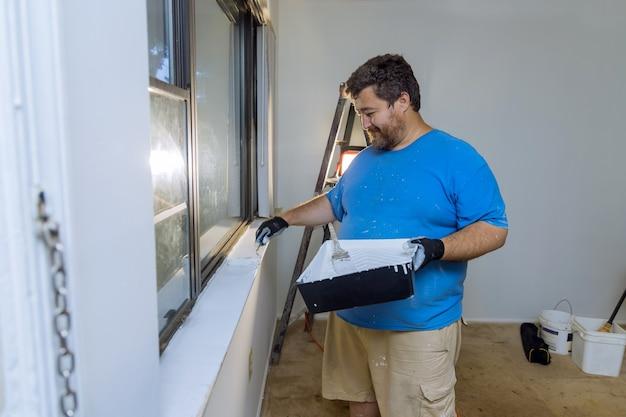 Złota rączka maluje ramę okna za pomocą wałka do malowania