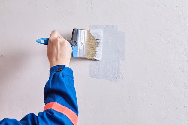 Złota rączka maluje ścianę za pomocą pędzla i koloru podczas remontu w domu