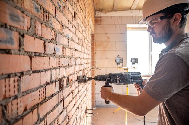 Złota rączka na budowie w trakcie wiercenia w ścianie perforatorem