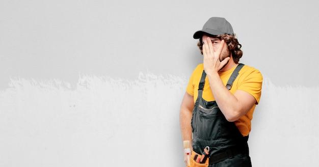 Złota rączka pracownik zakrywa jego twarz
