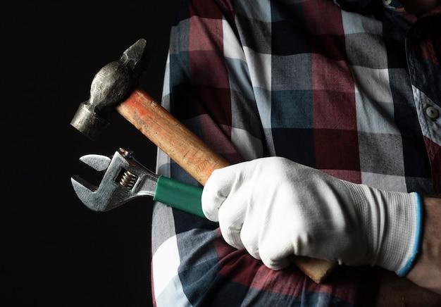 Złota rączka silna ręka w rękawice zbliżenie z młotkiem i kluczem narzędzia.