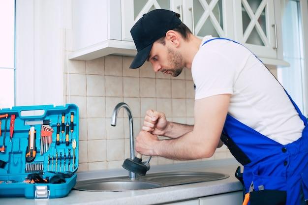 Złota rączka w mundurze czyści zatkany zlew kuchenny za pomocą popychacza