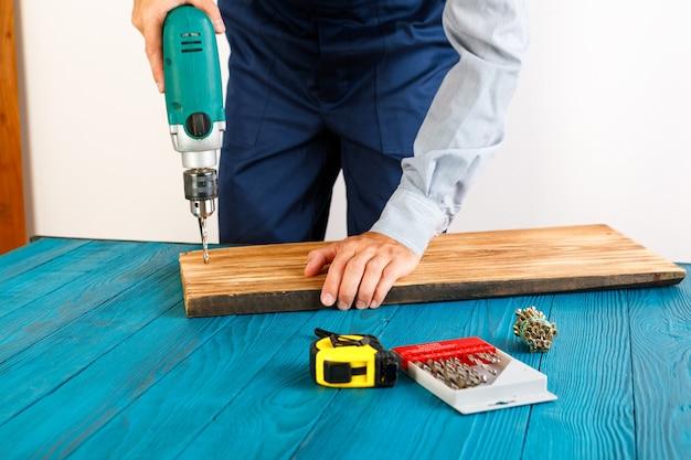 Złota rączka w niebieskim mundurze pracuje z automatycznym śrubokrętem elektrycznym. koncepcja remontu domu.
