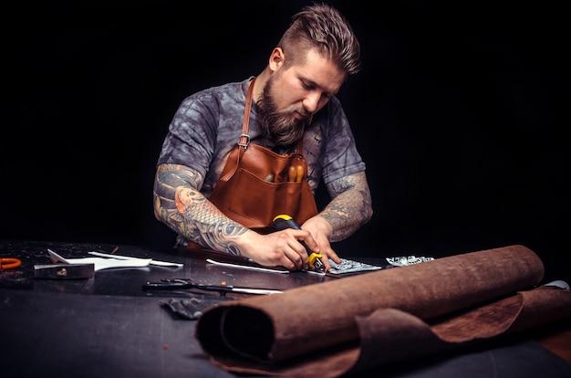 Złota rączka wycinająca skórzane kształty dla nowego produktu w miejscu pracy. tanner interesuje się swoim biznesem w warsztacie.