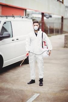 Złota rączka z insektycydem stoi przed jego van