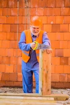Złota rączka z ręcznymi pracami stolarskimi pracownik budowniczy stolarz złota rączka z piłą pracownik budowlany