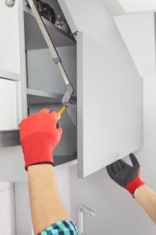 Złota rączka ze śrubokrętem montuje meble w kuchni pracownik ustawia drzwi na szarej szafce