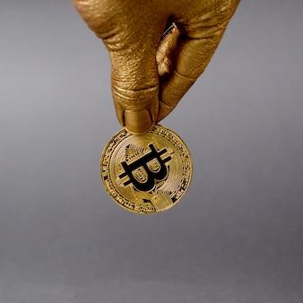Złota ręka trzyma fizyczną monetę kryptowaluty bitcoin.