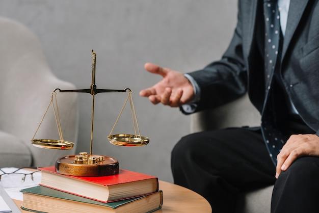 Złota skala na stosie książki przed męskim prawnika obsiadaniem na krzesła gestykulować