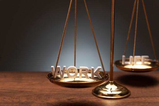 Złota skala równowagi mosiądzu na drewniane biurko i szare tło