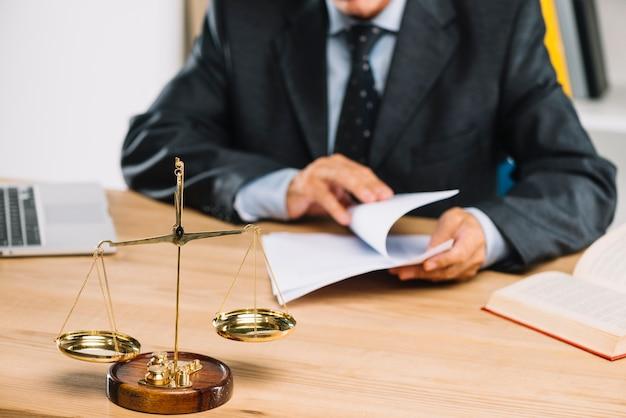 Złota skala sprawiedliwości przed prawnikiem, obracając strony dokumentu w sali sądowej