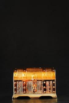 Złota skrzynia skarbów na czarnej powierzchni z miejsca na kopię