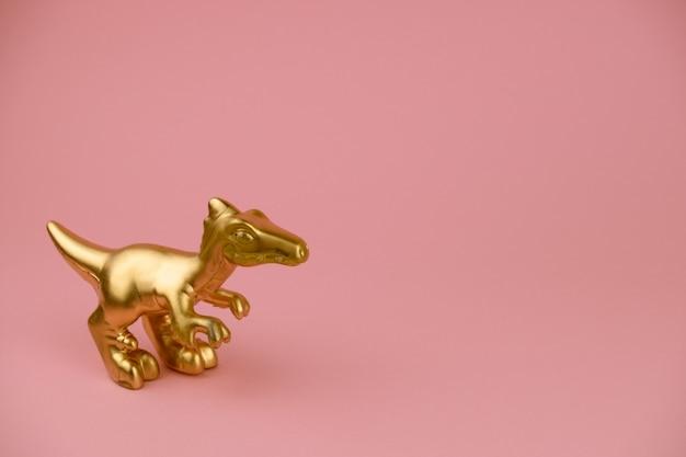 Złota statuetka dinozaura w pastelowym różu