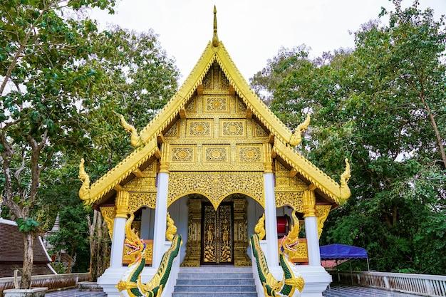 Złota świątynia przykrywa budynek drzewem w tle.