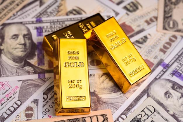 Złota sztabka na amerykańskich banknotach dolarowych, koncepcja towarów do obrony przed inflacją.