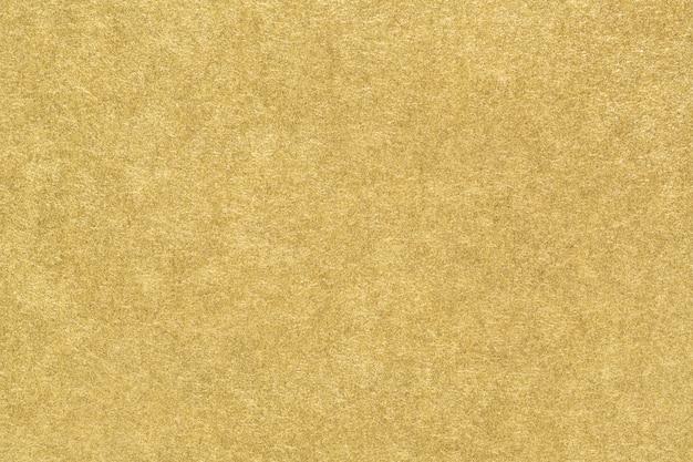 Złota tekstura papieru. gładka matowa złota folia streszczenie tło. zbliżenie.