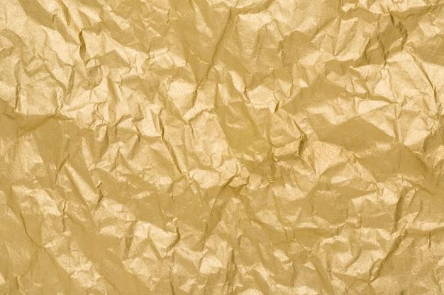Złota tekstura papieru. pomarszczony matowy złotej folii abstrakcyjne tło.