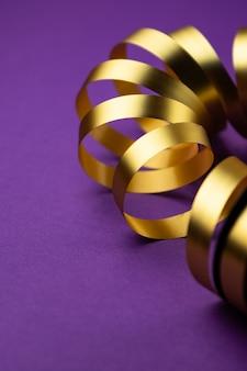 Złota wakacyjna wstążka na fioletowej matowej powierzchni