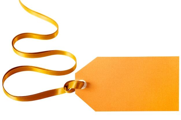 Złota wstążka prezentowa i pomarańczowa metka