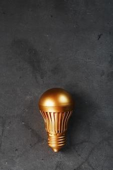 Złota żarówka na czarnej teksturowanej powierzchni