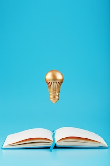 Złota żarówka w lewitacji z otwartego notatnika na niebiesko.