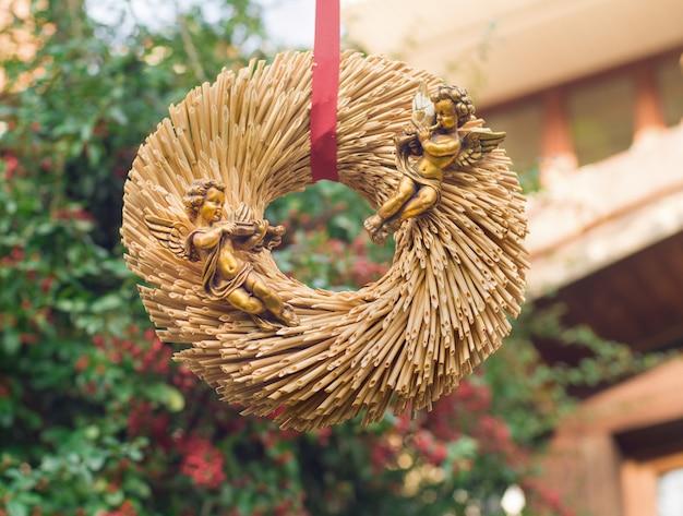 Złote anioły na słomianym wieńcu na walentynki lub boże narodzenie