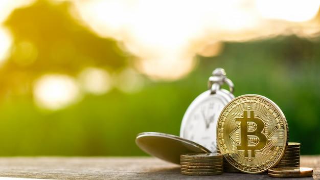 Złote bitcoiny i stary zegarek kieszonkowy w stosie złotych monet na stole.