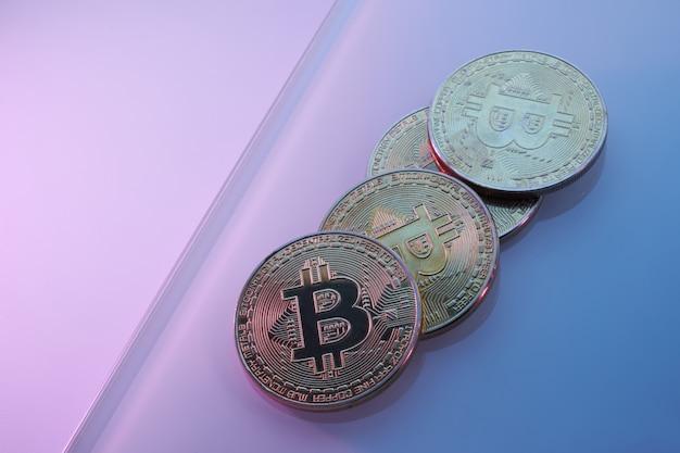 Złote bitcoiny izolowane na neonowym niebieskim, różowym, fioletowym tle zbliżenie z miejscem na kopię, koncepcją wzrostu i upadku kryptowaluty