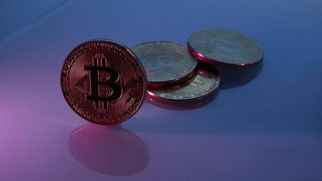 Złote bitcoiny izolowane na zbliżeniu neonowego niebieskiego różowego fioletowego tła z miejscem na kopię, koncepcją wzrostu i upadku kryptowaluty