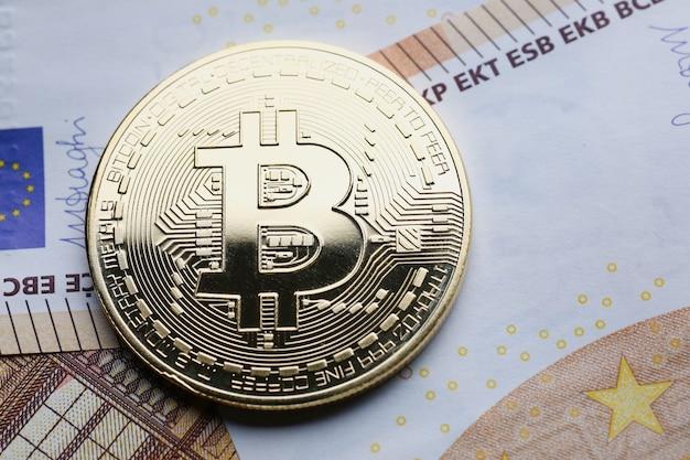 Złote bitcoiny na banknotach euro