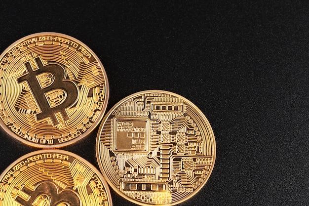 Złote bitcoiny na czarnym tle. pojęcie handlu kryptowaluty