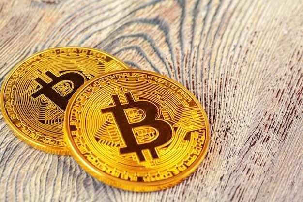 Złote bitcoiny na drewnianym stole.