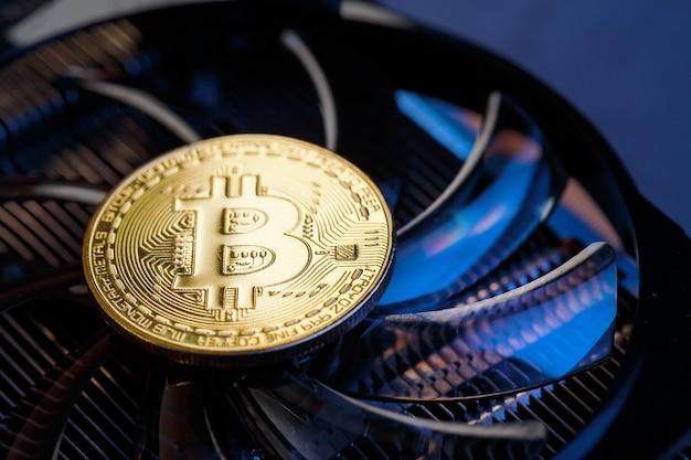 Złote bitcoiny na karcie graficznej z niebieskim podświetleniem w stylu cyberpunk. kryptowaluta. koncepcja wydobywania bitcoinów