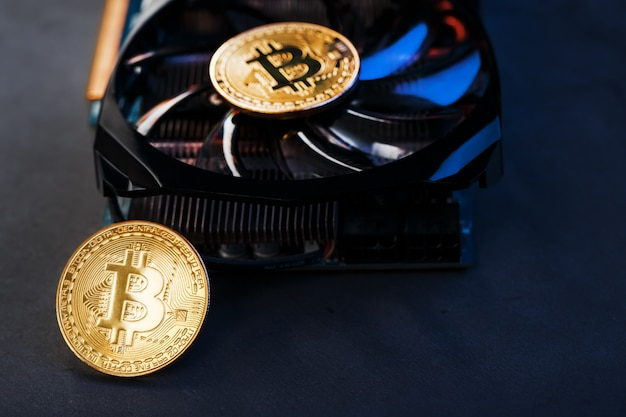 Złote bitcoiny na karcie graficznej z niebieskim podświetleniem w stylu cyberpunk