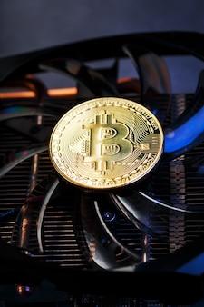 Złote bitcoiny na karcie graficznej z niebieskim podświetleniem