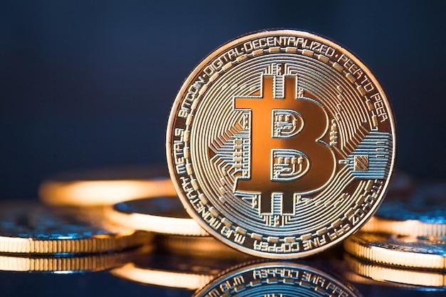 Złote bitcoiny na niebieskiej powierzchni