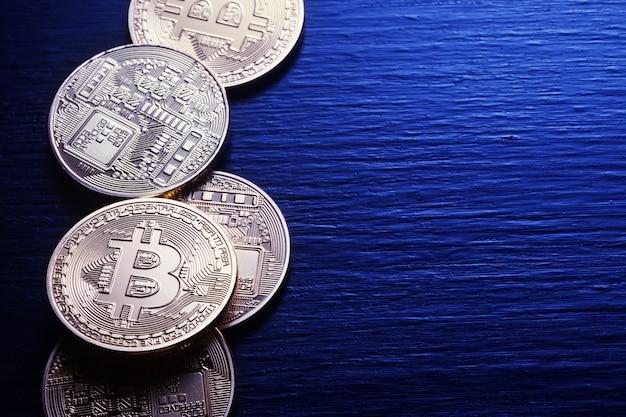 Złote bitcoiny na teksturowanej drewnianej ścianie