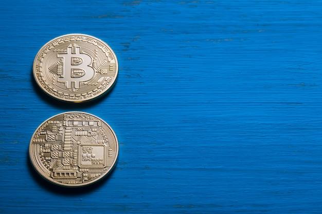 Złote bitcoiny na teksturowanej niebieskiej drewnianej ścianie