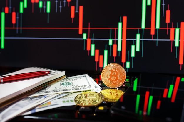 Złote bitcoiny na tle wykresów biznesowych z bliska i 100 banknotów dolarowych.