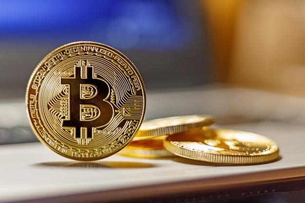 Złote bitcoiny na zbliżenie touchpada laptopa. wirtualne pieniądze kryptowaluty