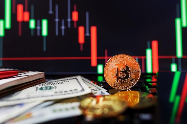 Złote bitcoiny na zbliżeniu wykresów biznesowych i 100 dolarowych banknotów.