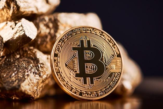 Złote bitcoiny obok złotych brył