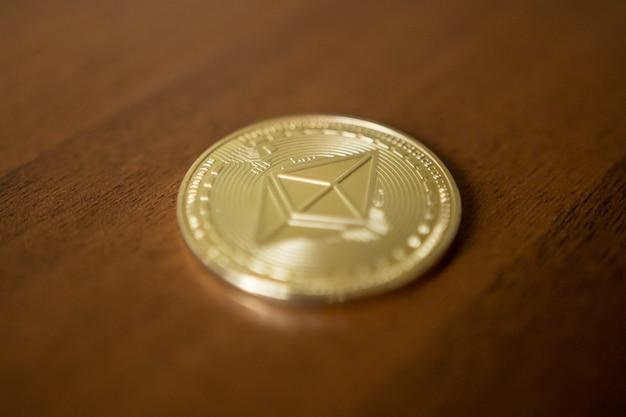 Złote bitcoiny są ułożone na jasnym tle zbliżenia wykresów biznesowych